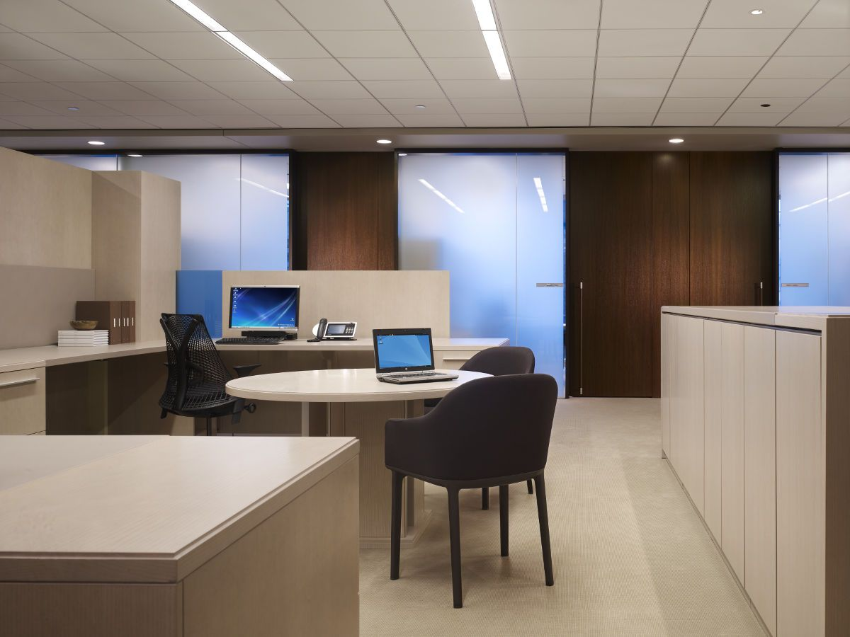 A double workstation features a shared round table for collaboration.