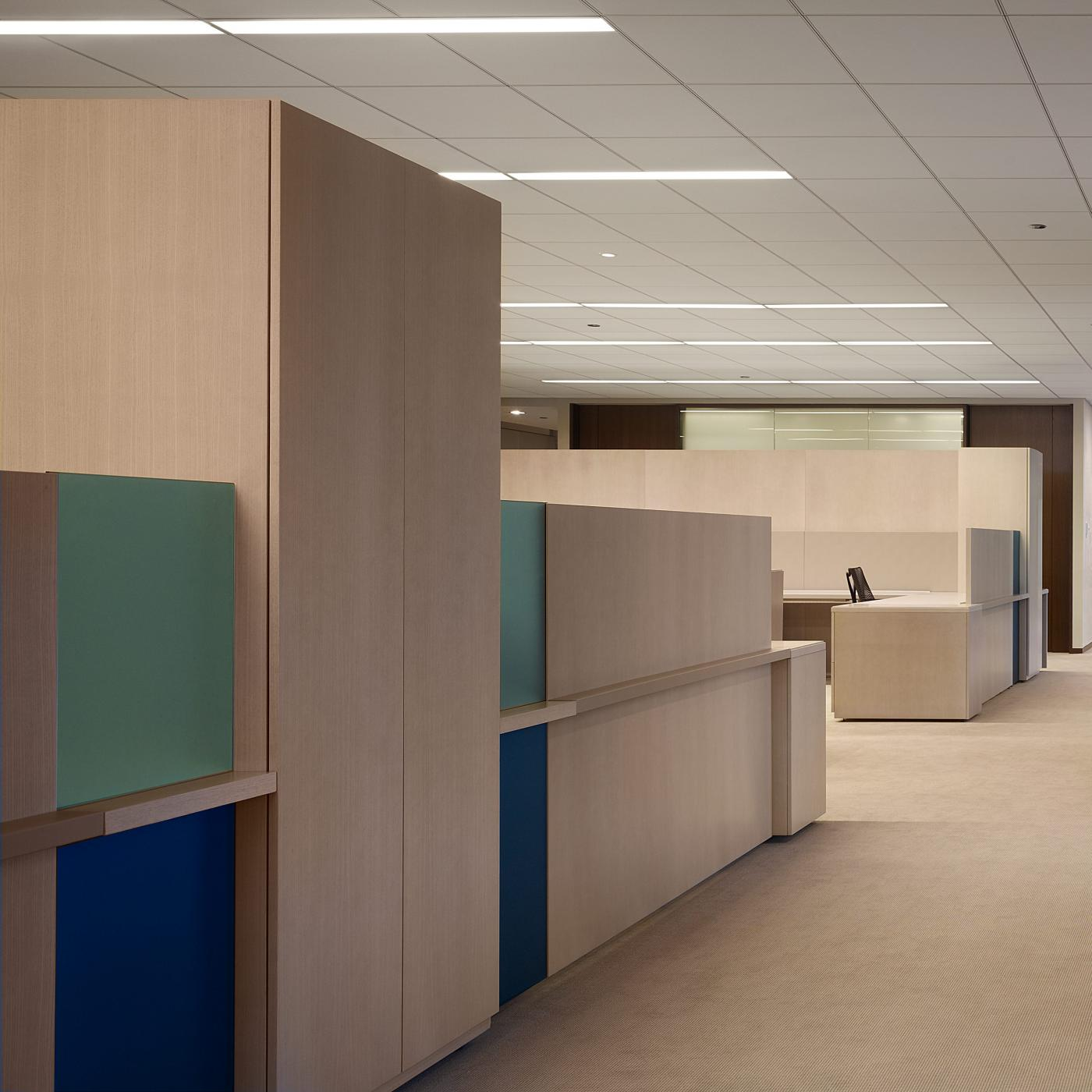 This open office seamlessly integrates wood veneers with leather and specialty glass.
