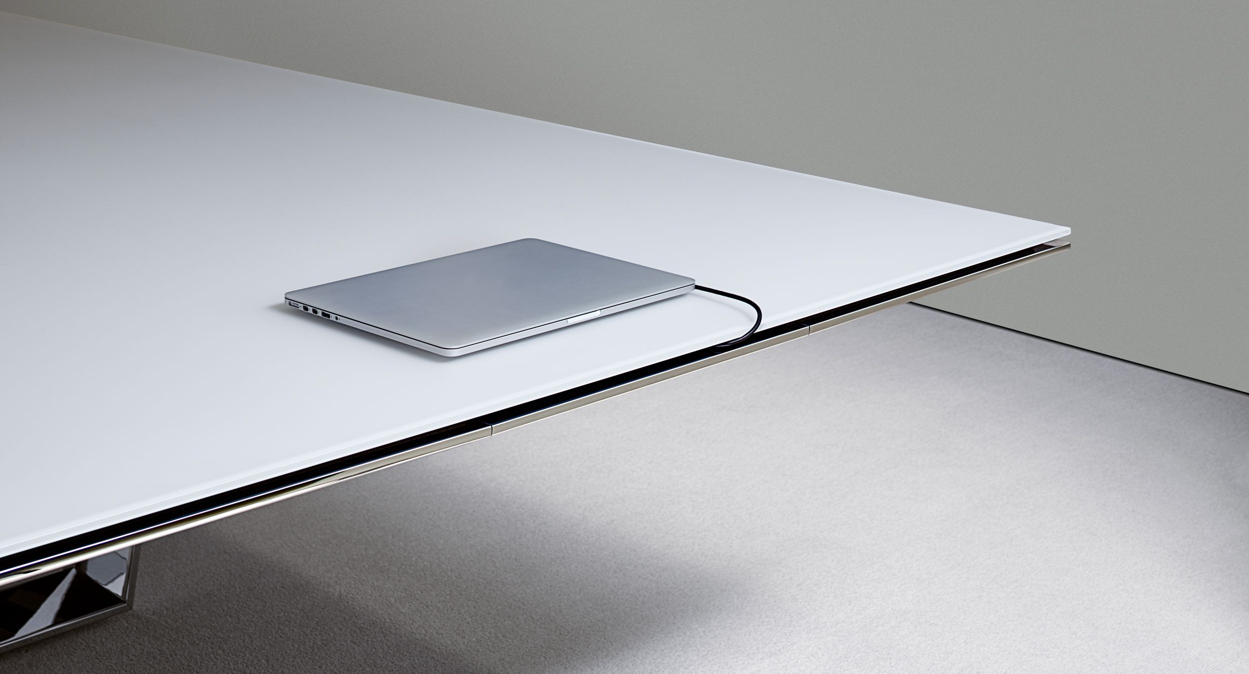Cables exit gracefully from a continuous edge reveal above the concealed drawer, eliminating the typical mess of wires.
