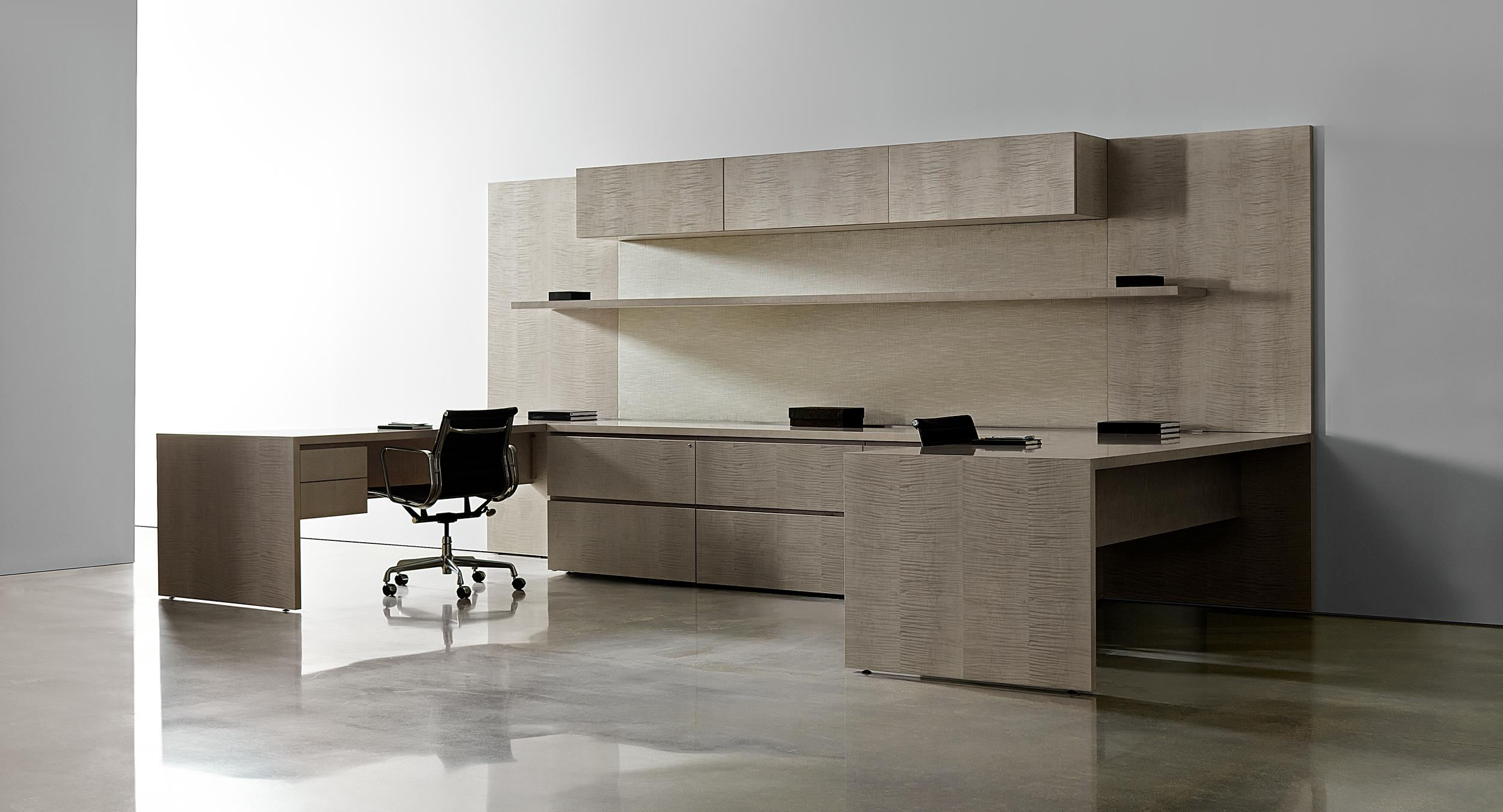 New Millennia features continuous open shelving, minimalist closed storage, and desking with raised storage and mitered joinery.
