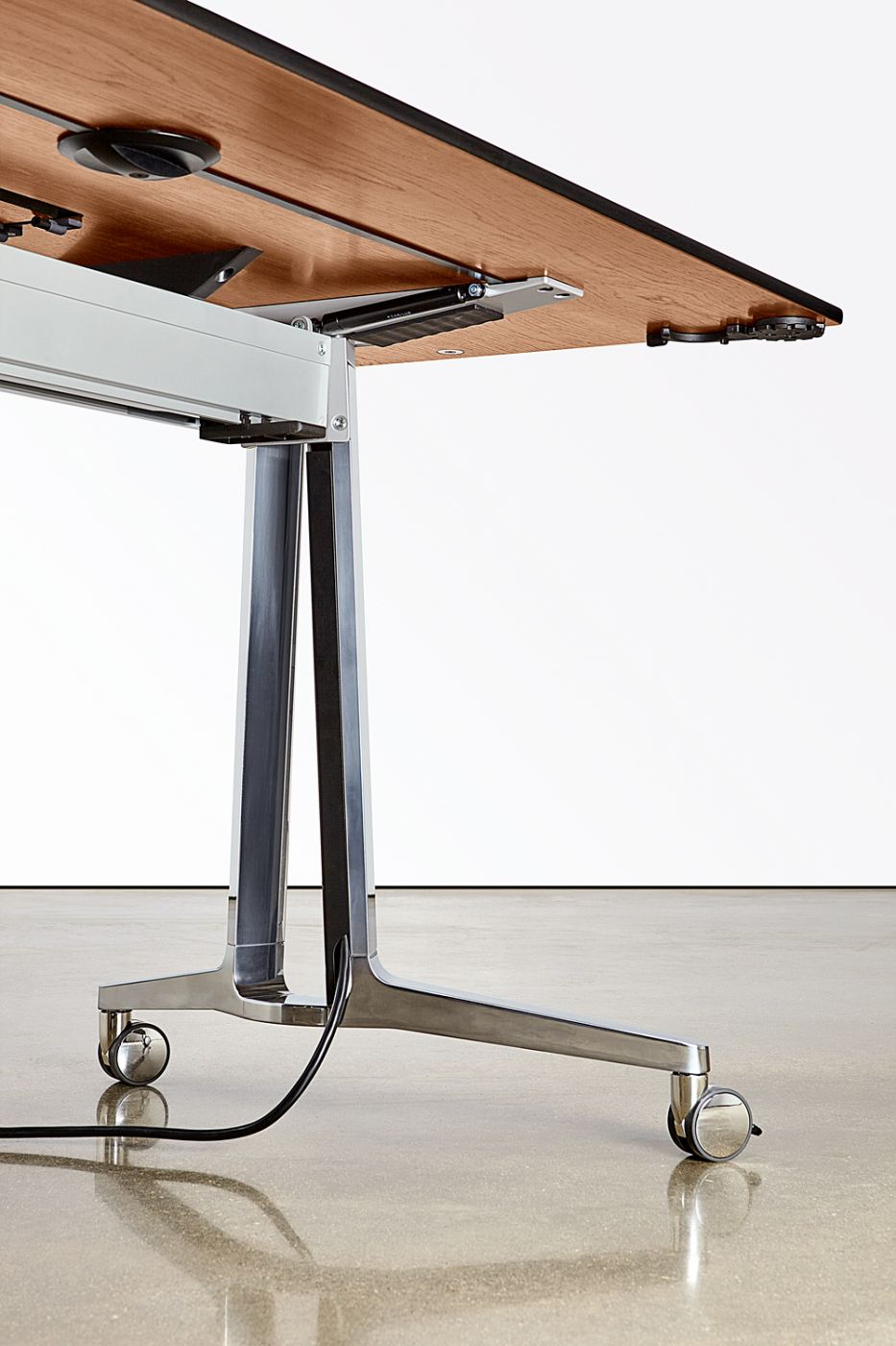 A minimalist leg wire chase hides cables for powered mobile tables.