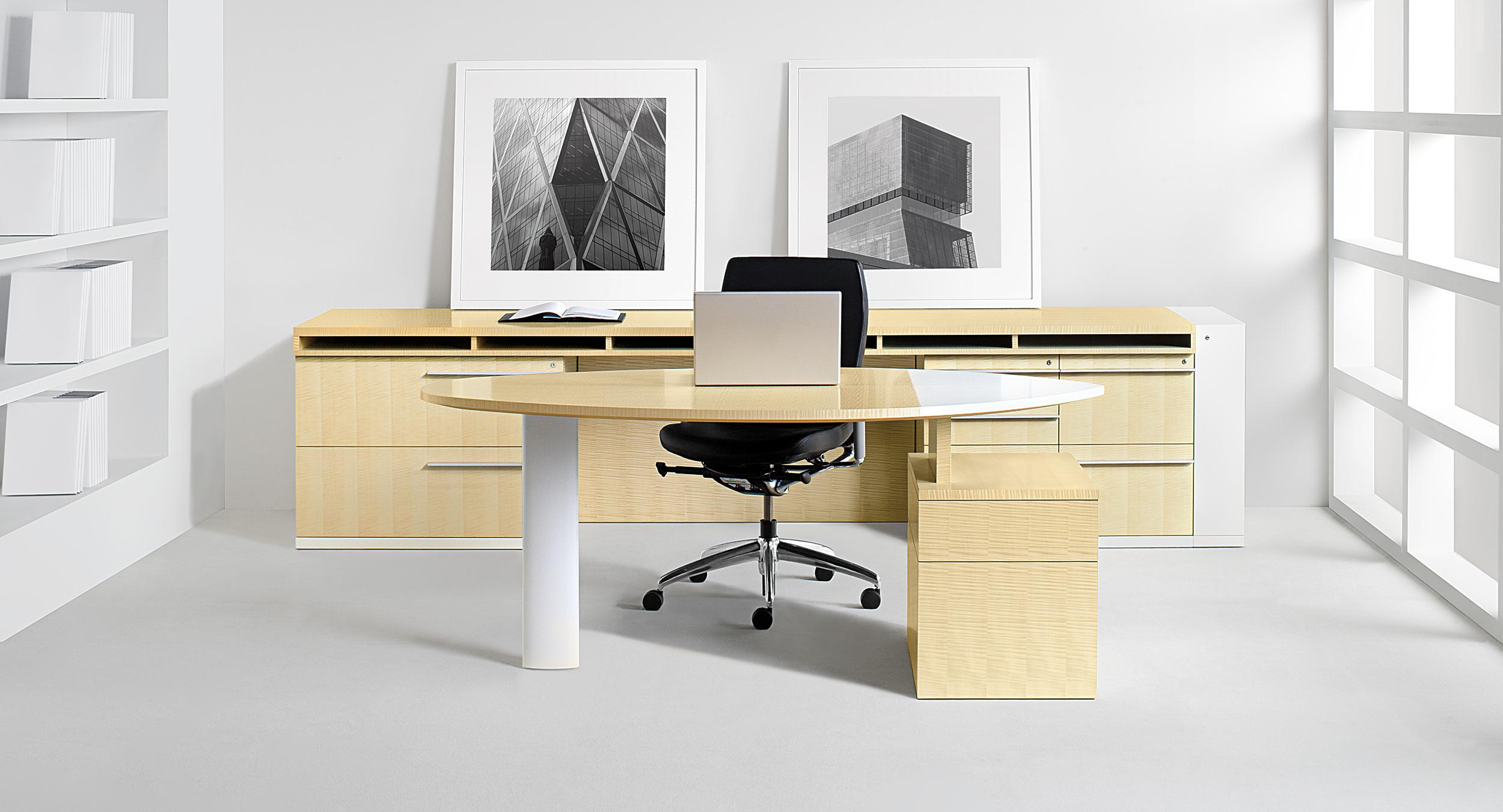 A light-scale desk sits in front of a storage credenza.   The credenza surface includes project slots for active paperwork.
