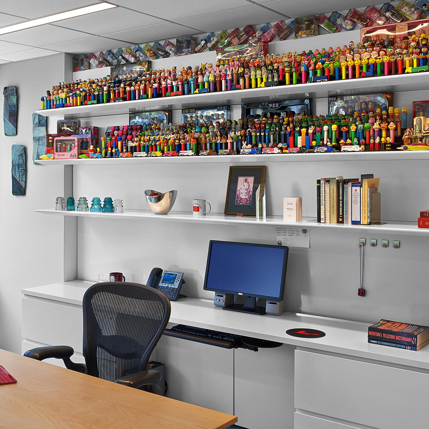 A brilliant PEZ dispenser collection is displayed on a white HALCON workwall with magnetic backsplash.