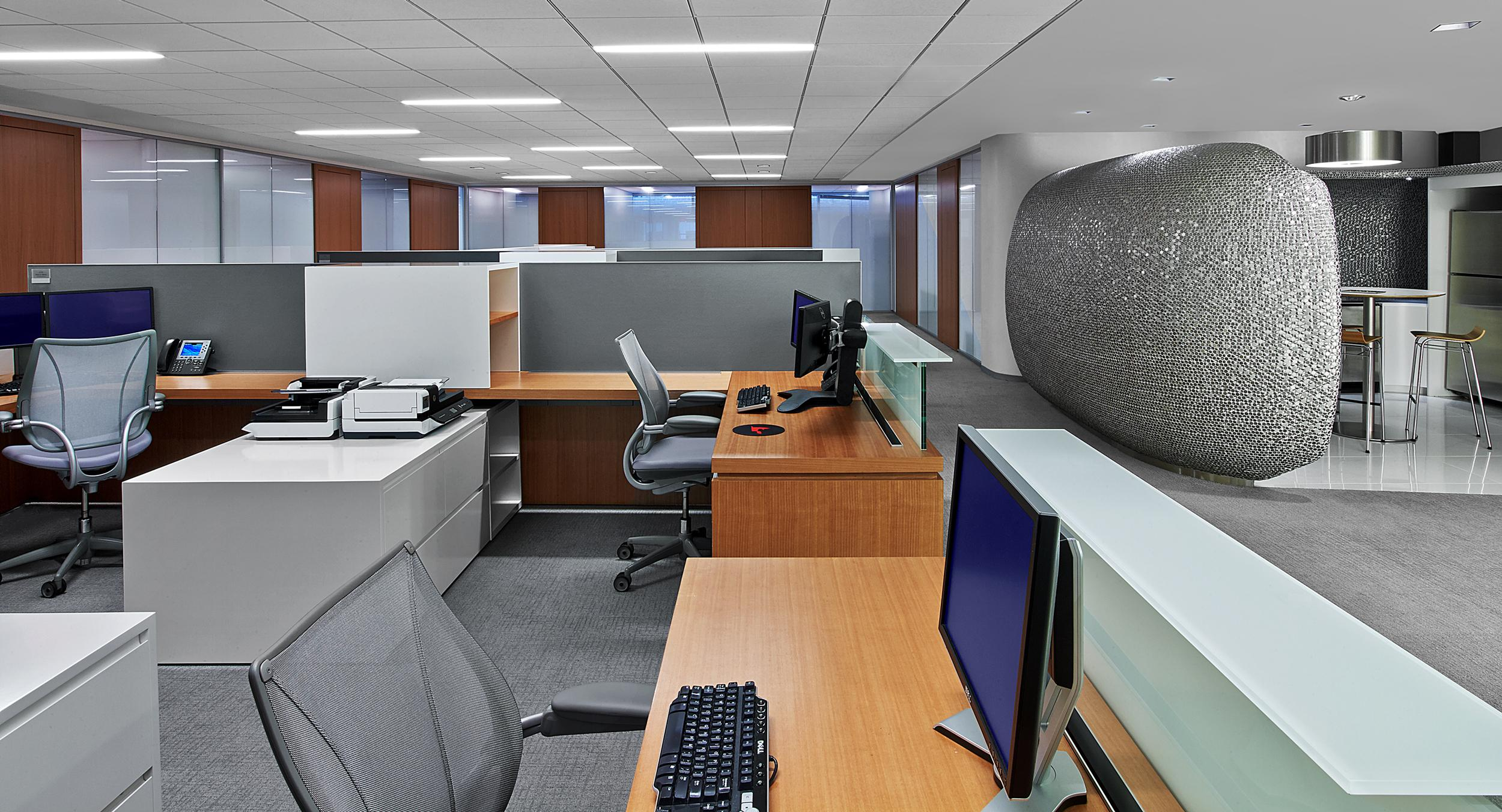 Custom-designed workstations incorporate anigre veneers with white casework, aluminum-framed Forbo screens, and floating glass transaction counters.