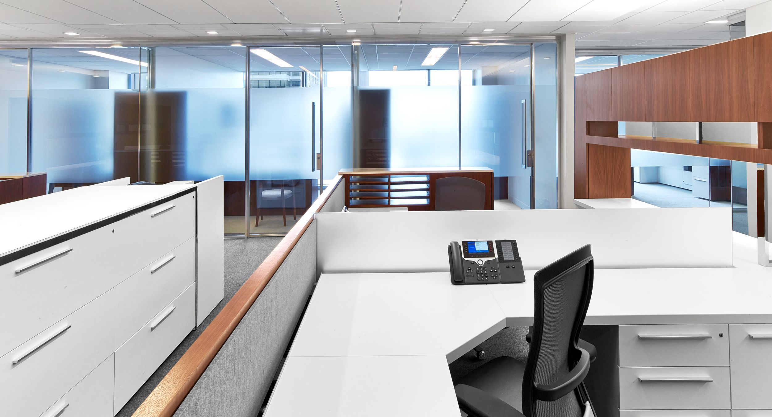 Workstations feature a full range of materials with walnut veneers, laminate, chrome, fabric, etched glass, and stone.