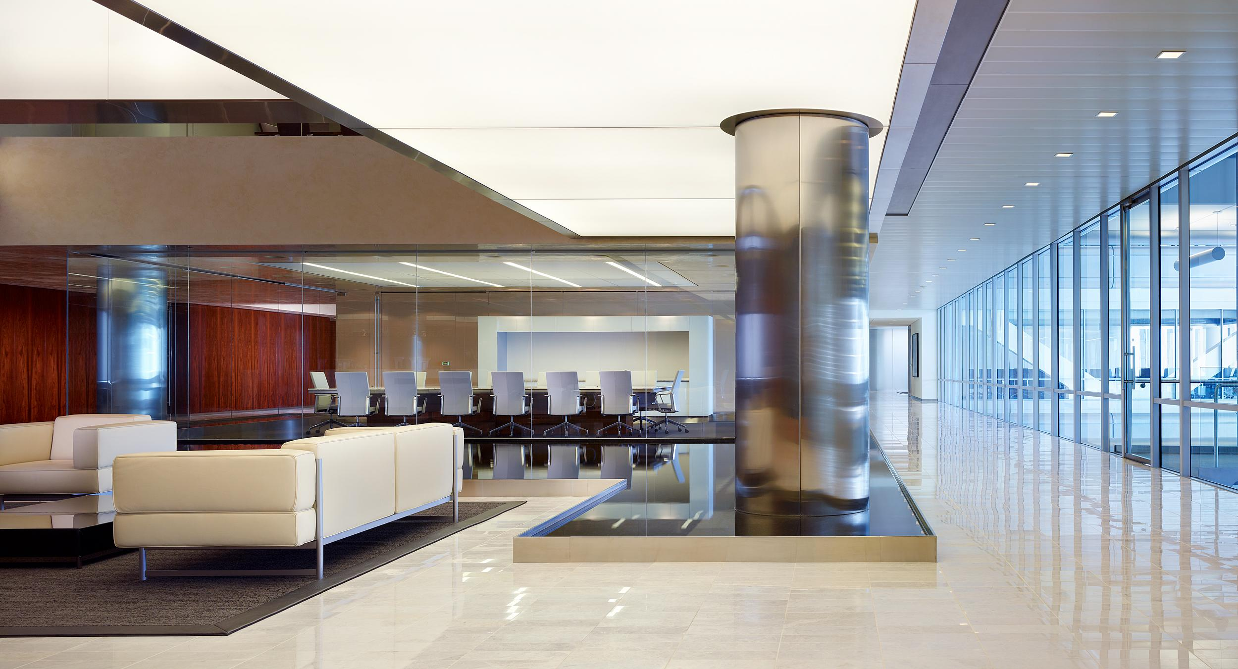 A shallow pool sits between Baker & McKenzie's lobby and a HALCON conference room.