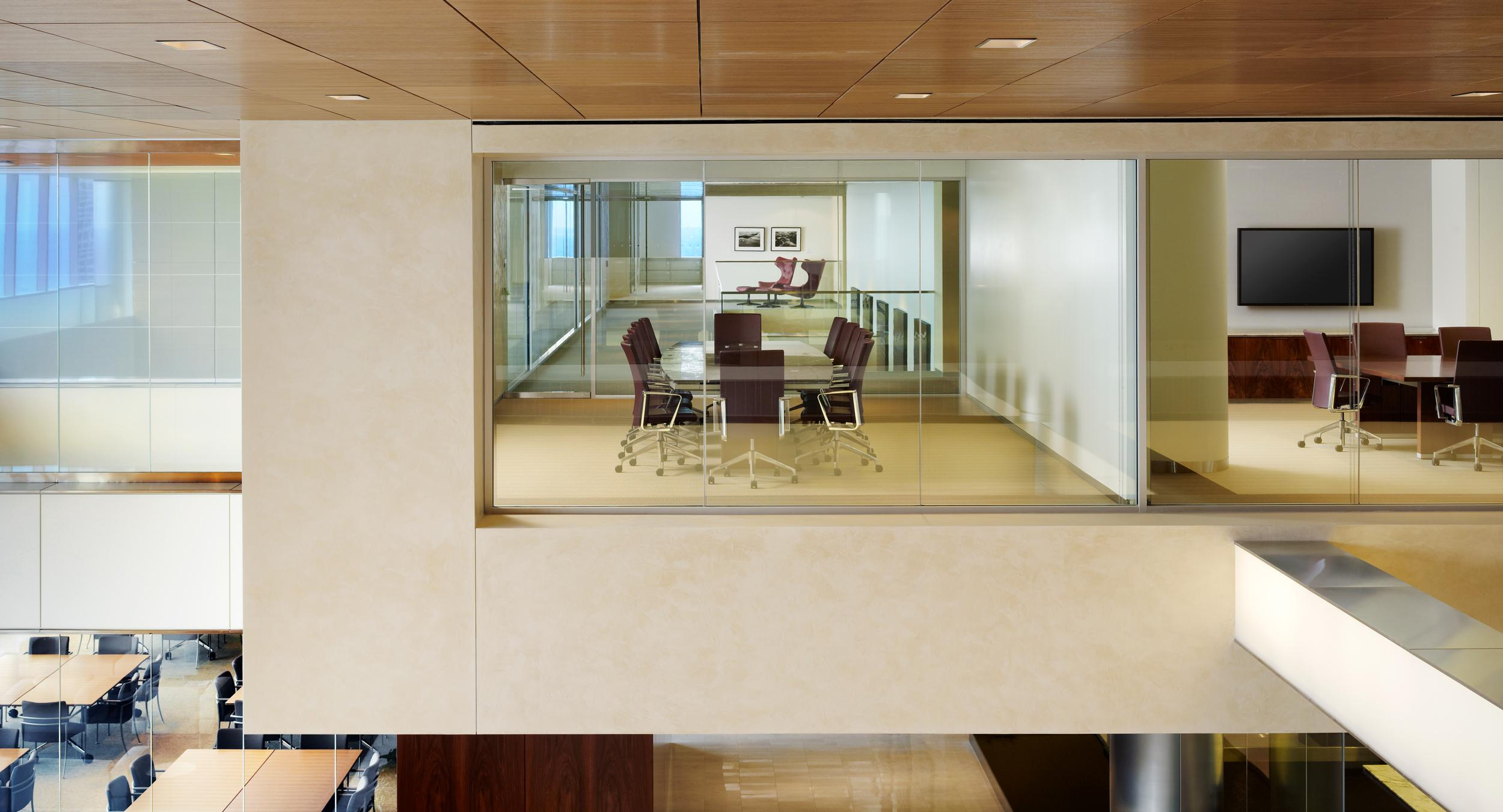 Glass-walled conference rooms overlook airy, beautiful space.