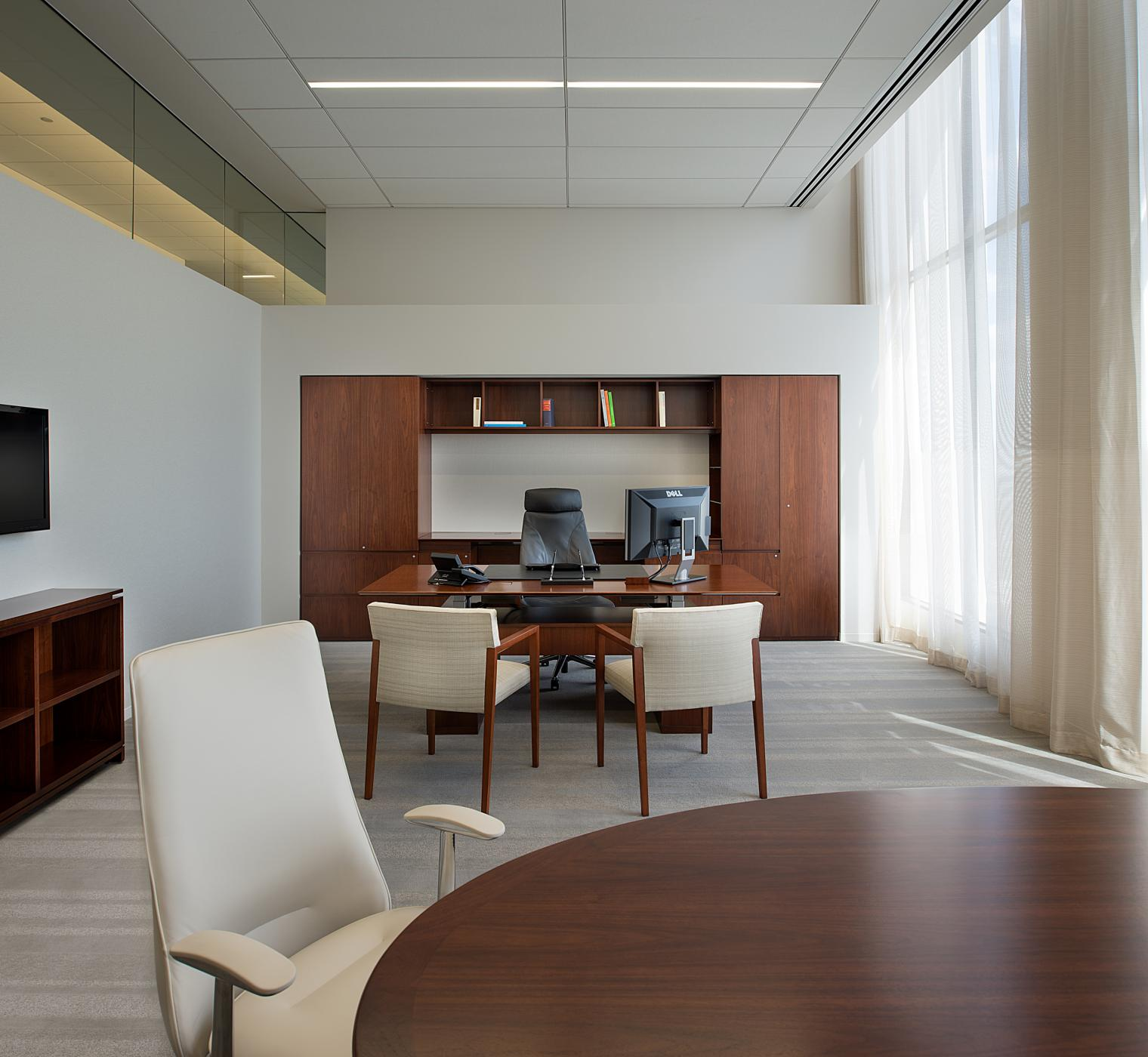 Each private office features a custom built-in workwall, meeting table, bookcase, and sit-to-stand desk.