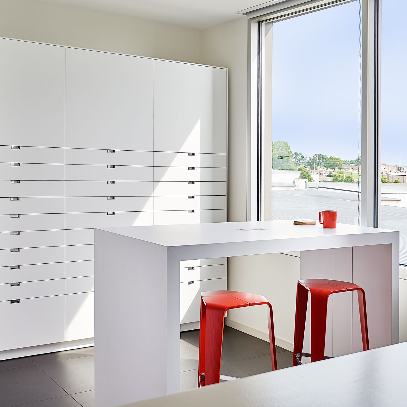 Our sample room features custom LEX storage and HUGO table in Designer White.