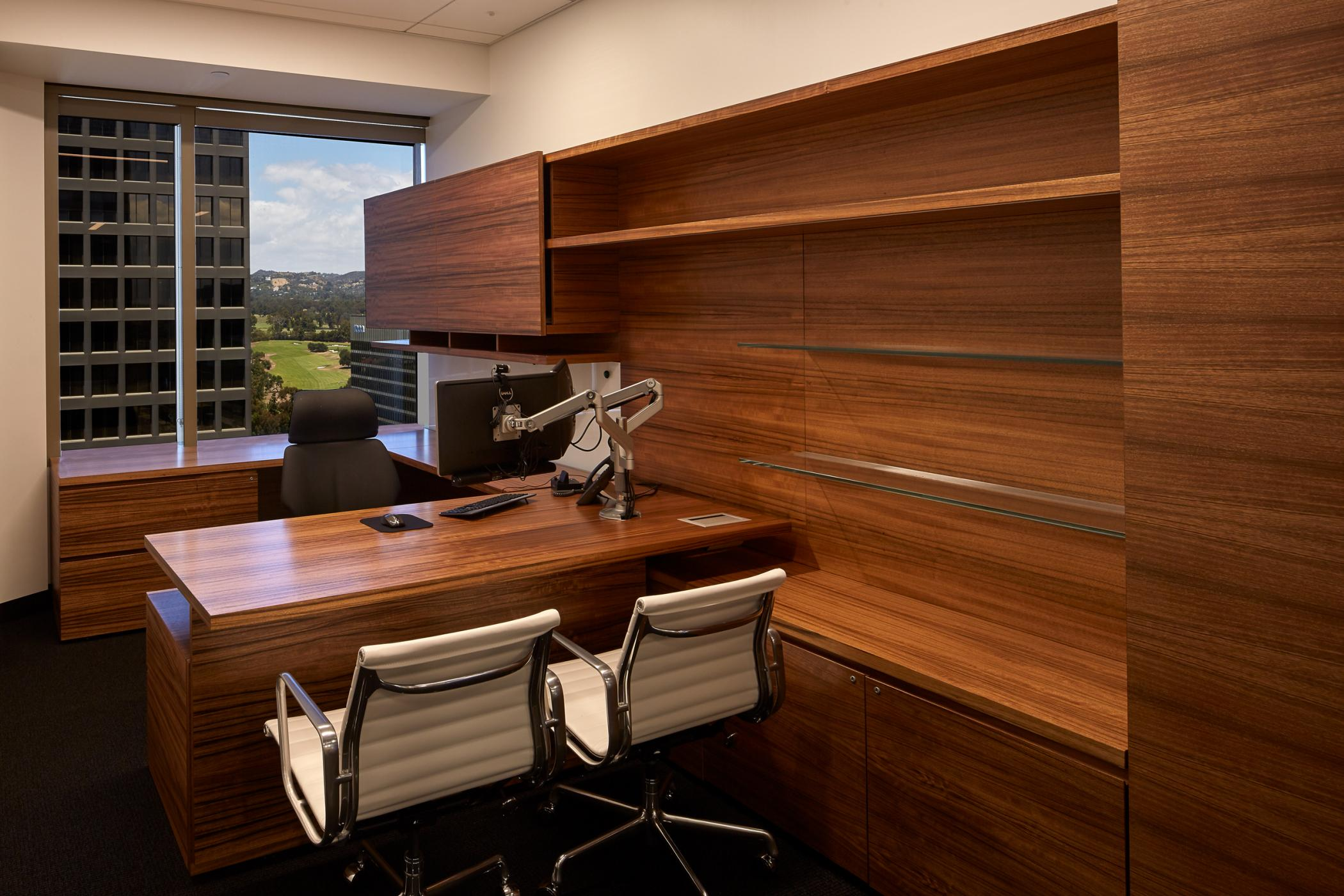 New Millennia offices integrate adjustable-height desking and floating glass shelves with horizontal-grain veneer casework.