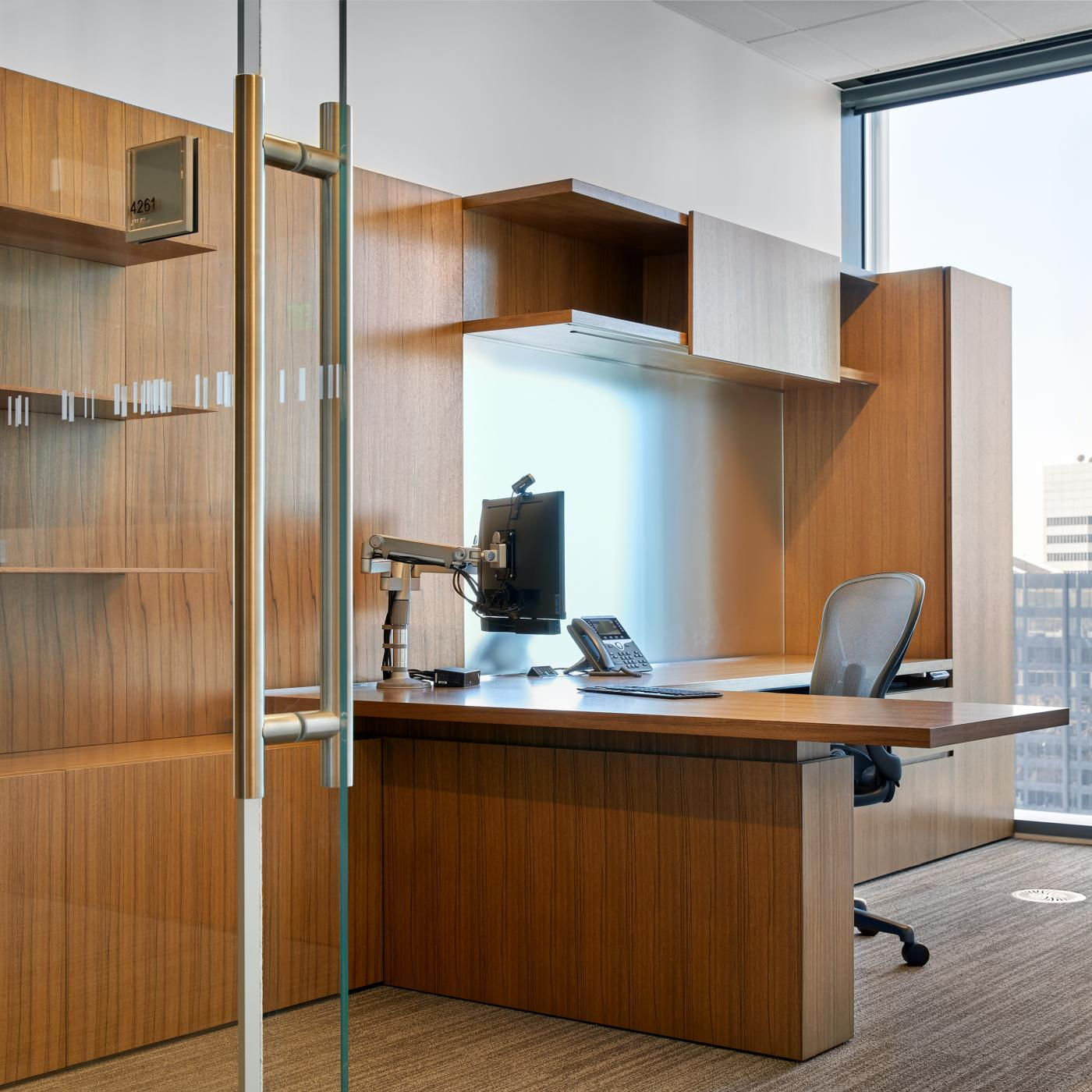 Universal-sized offices feature NEW MILLENNIA with Paldao veneers, etched mirror glass, and adjustable-height worksurfaces.