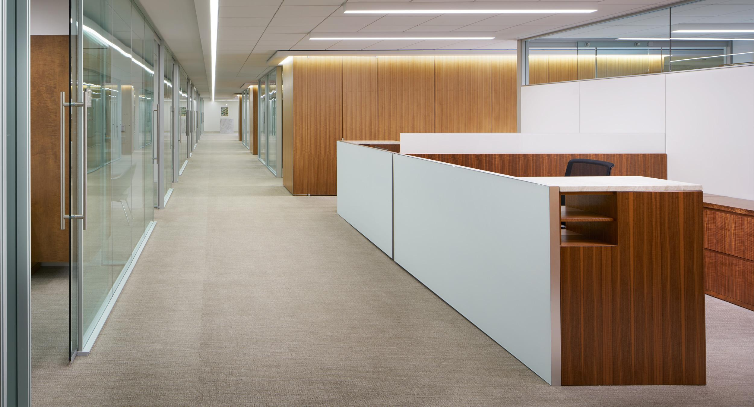 Administrative workstations feature stone, etched glass, and figured walnut veneers.