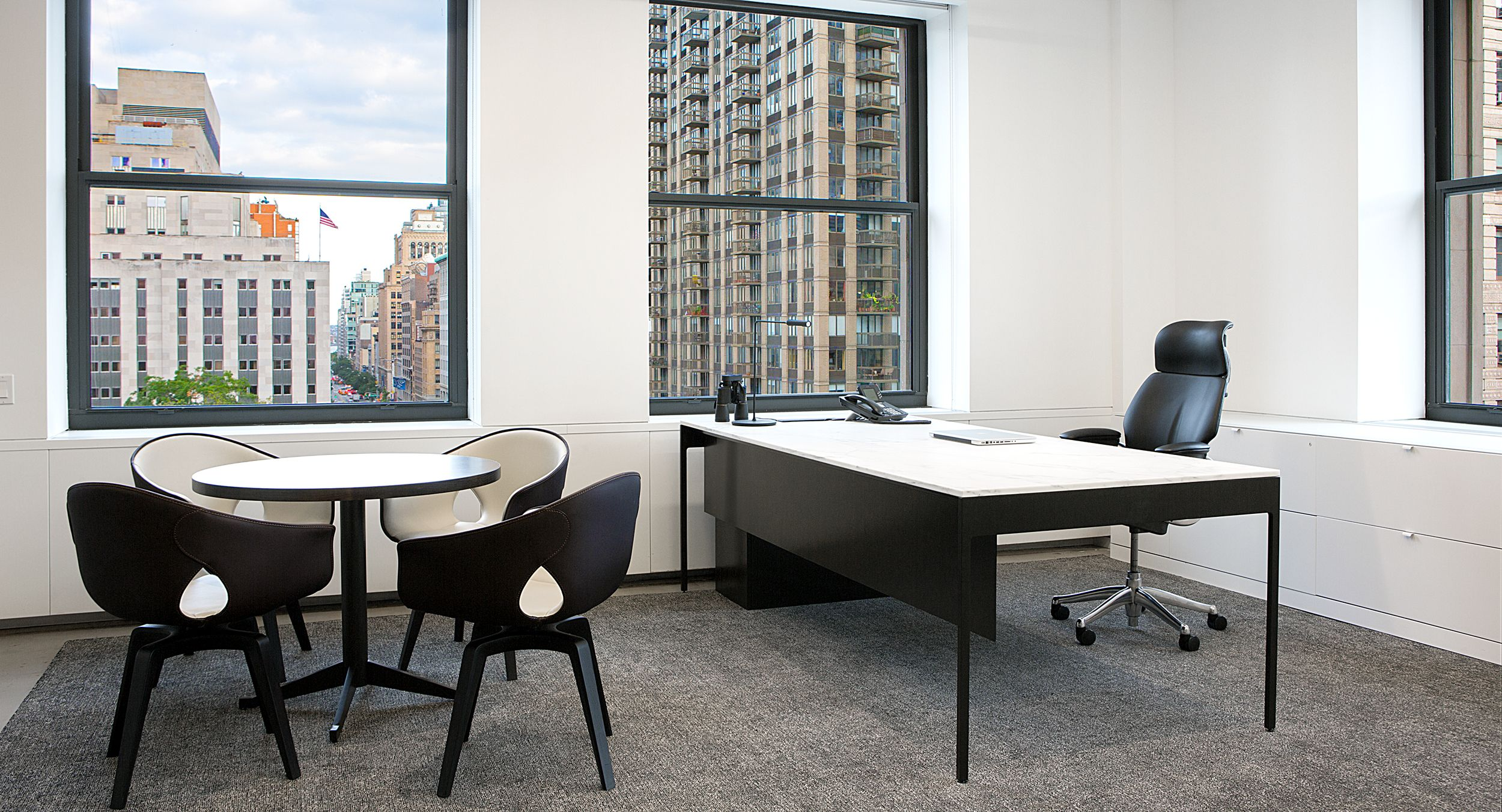 Private offices feature White Corian and glass paired with bronze table legs.