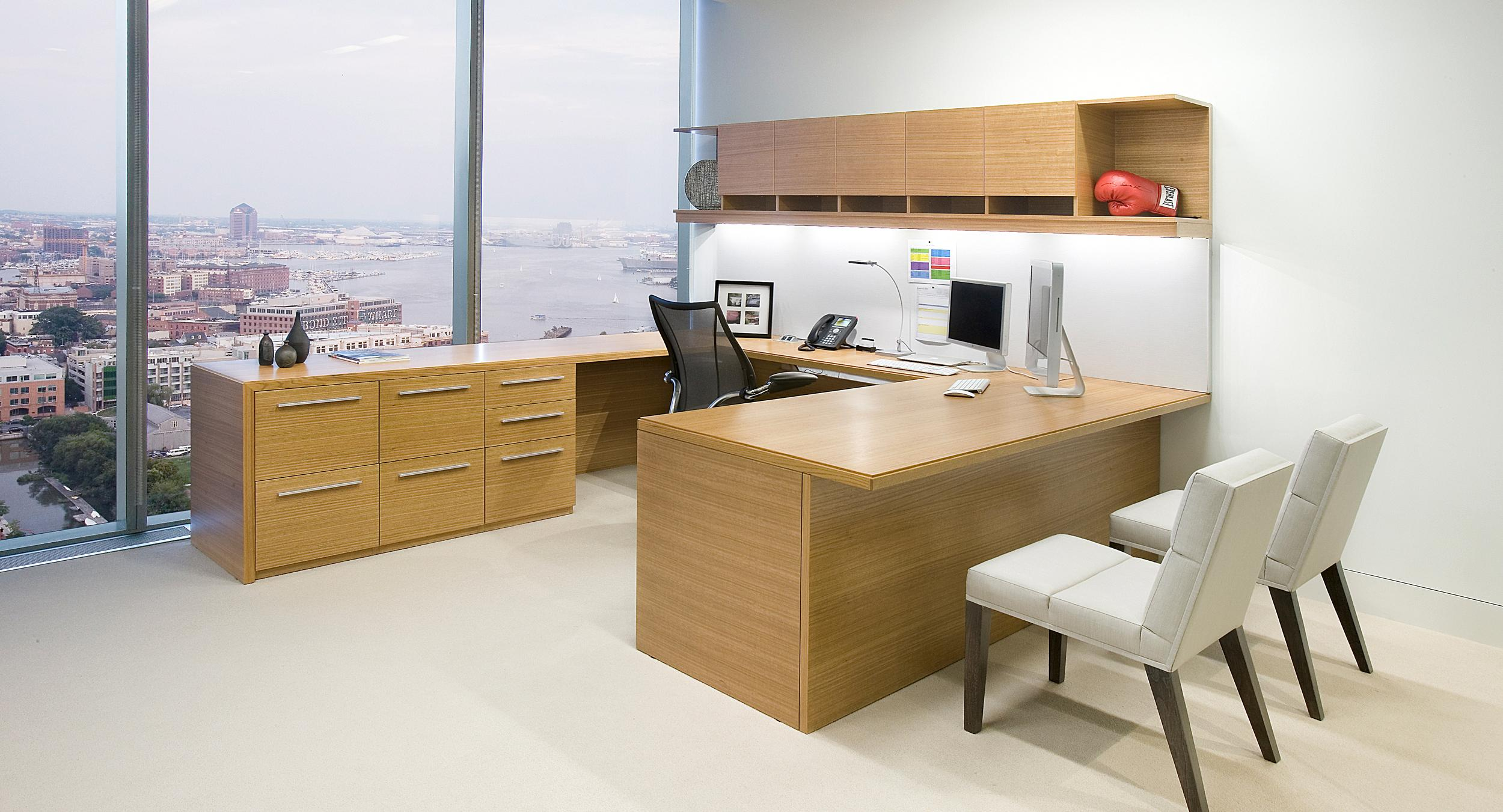 Custom Mitre private offices showcase beautifully-matched horizontal eucalyptus veneer.
