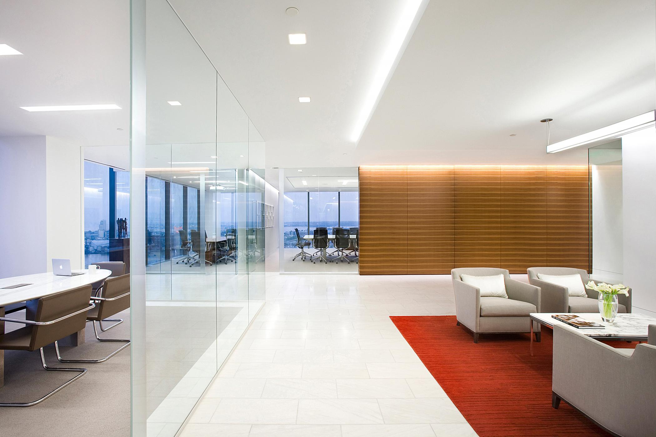 Three conference tables of varying shapes, materials, and design are visible from the lobby.