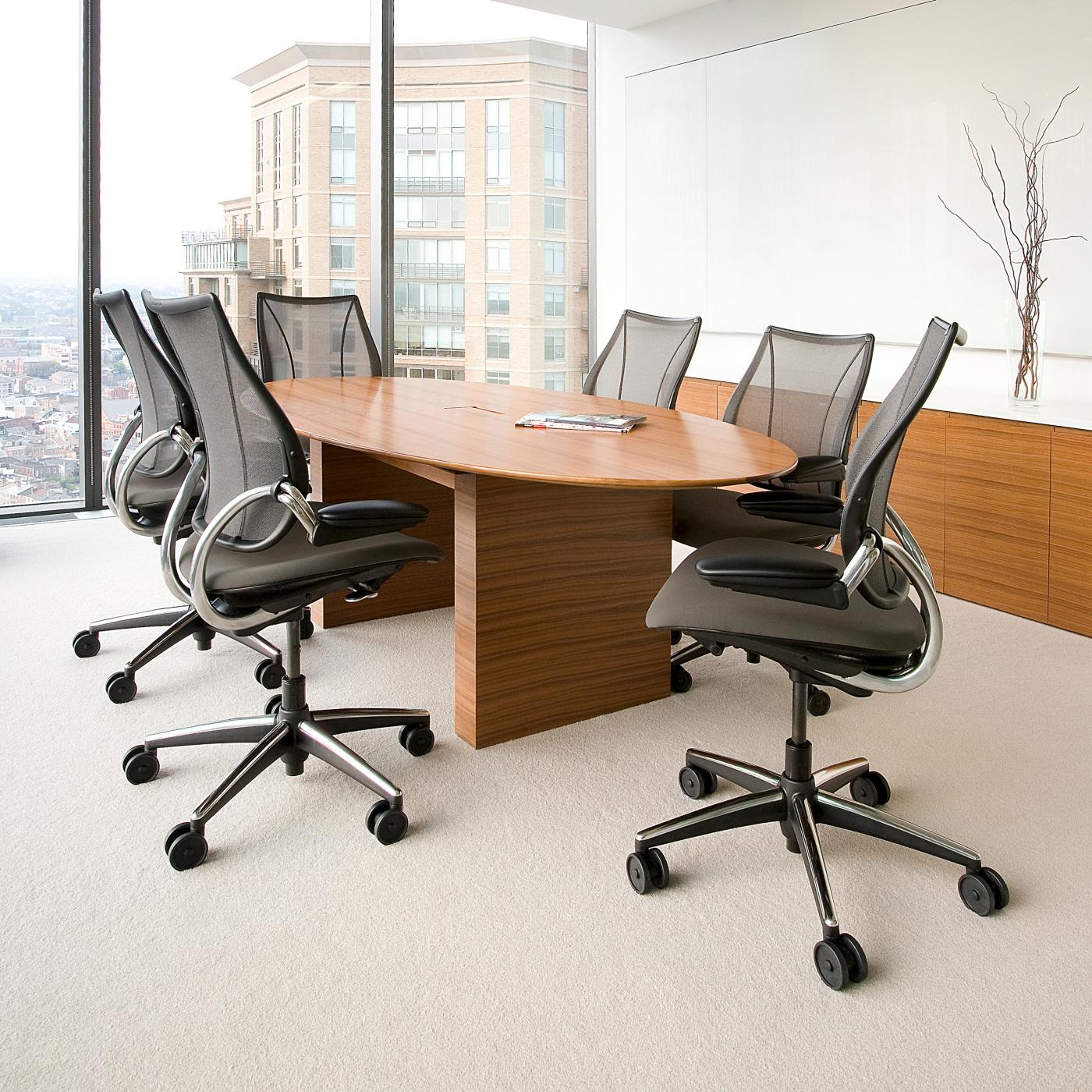 An elliptical conference table in eucalptus veneer matches the credenza with stone surface.