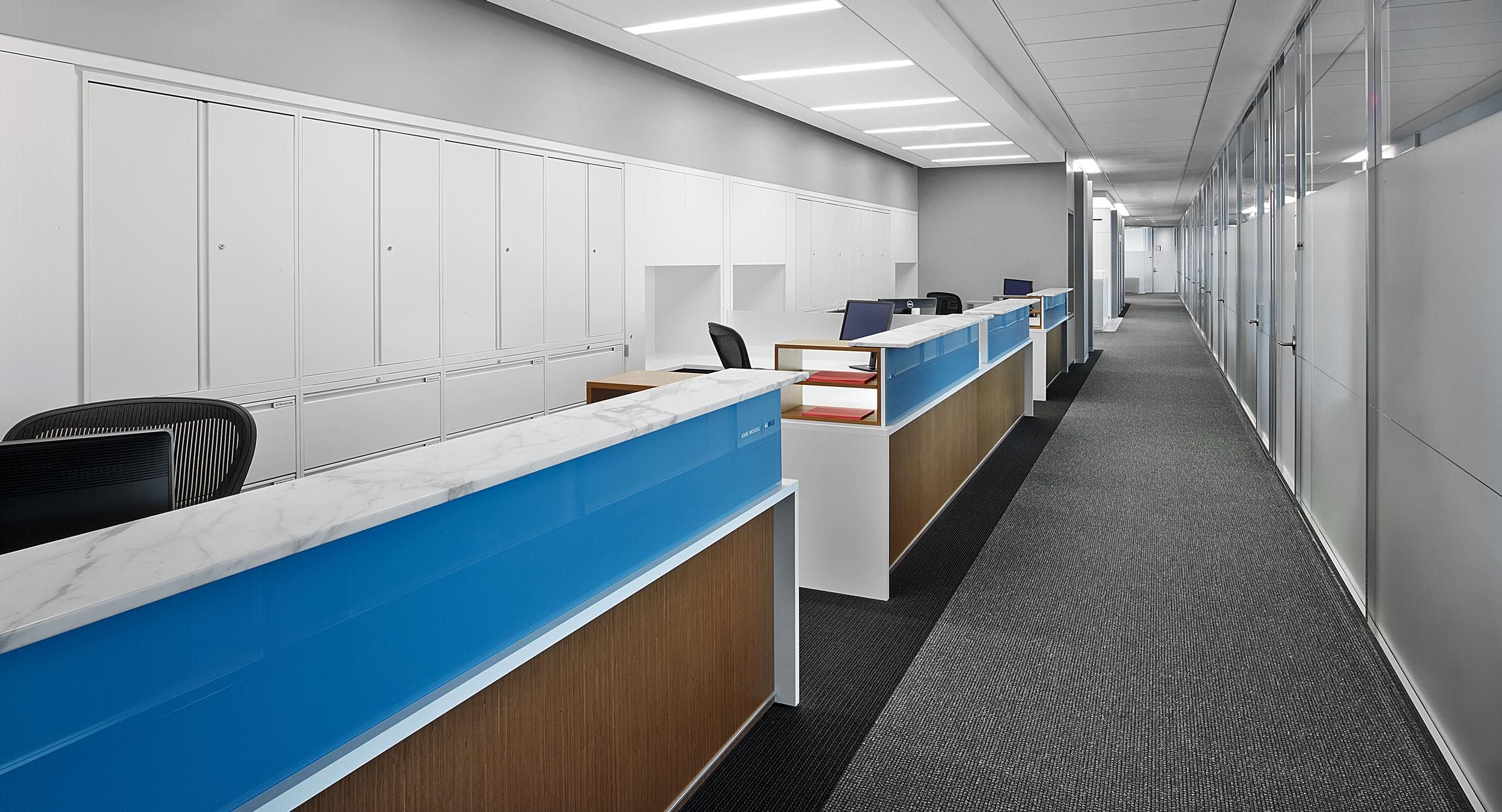 Administrative stations featured stone transaction counters, blue tinted glass, frosted acrylic privacy screen, white laminate and wood surround panels with satin aluminum base accent trim.