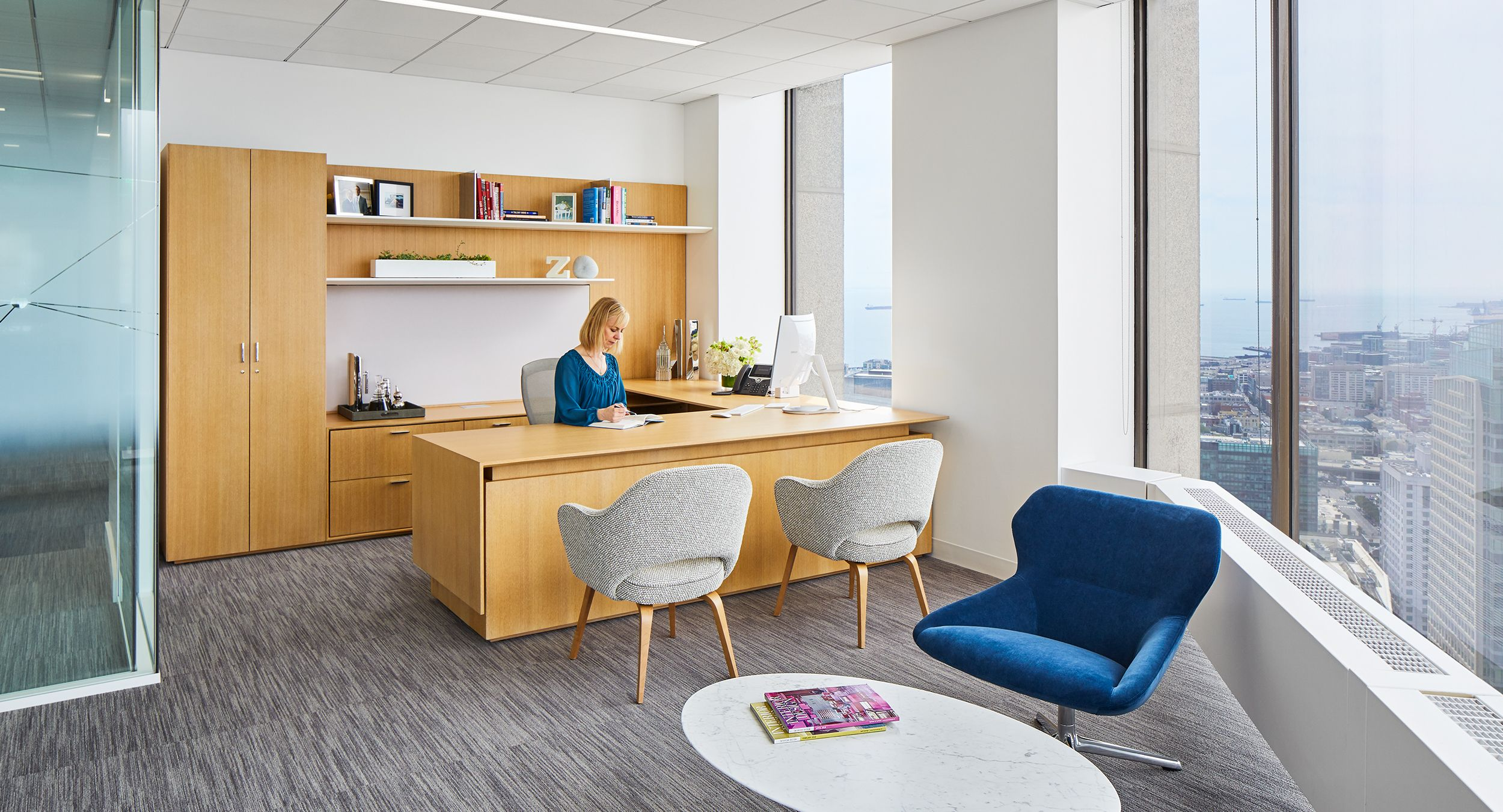 Beautiful private offices feature custom-designed adjustable-height desking in Rift White Oak.