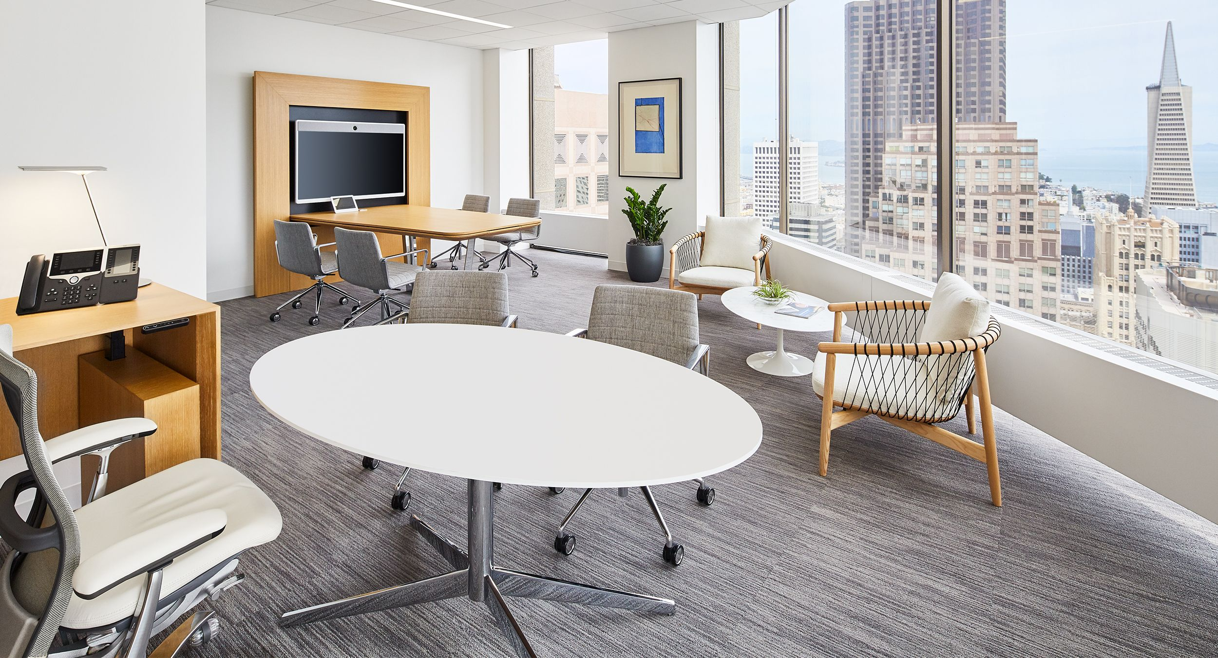 This SESSIONS elliptical table features a Modern White Corian® surface and a MESA media wall is finished in Rift White Oak and Polished Chrome.