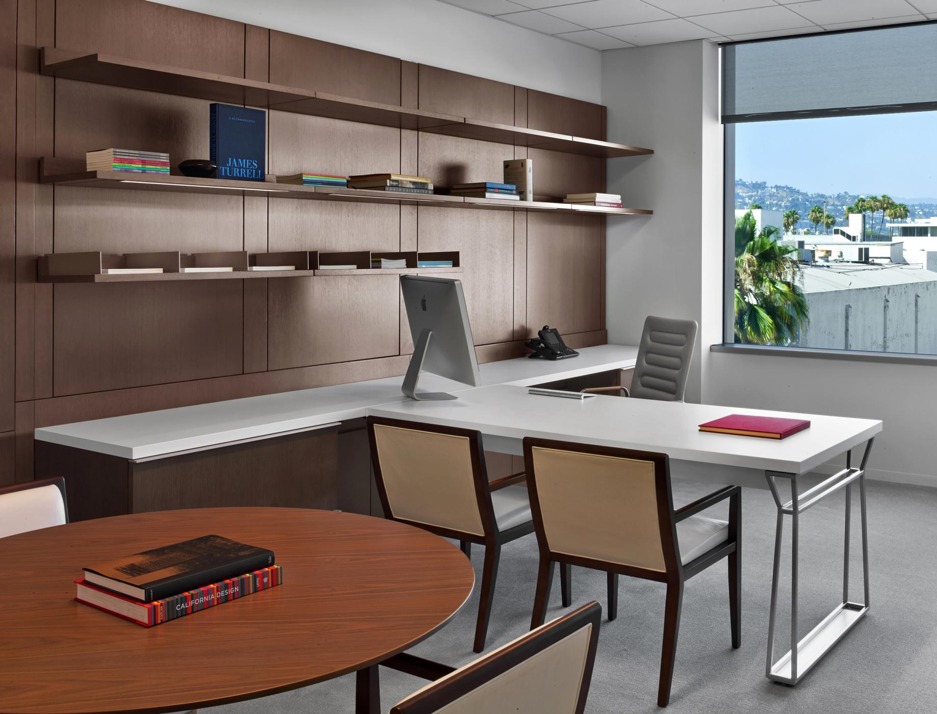 Private offices feature rift oak workwalls, Smoky White laminate surfaces, and brushed aluminum hardware.