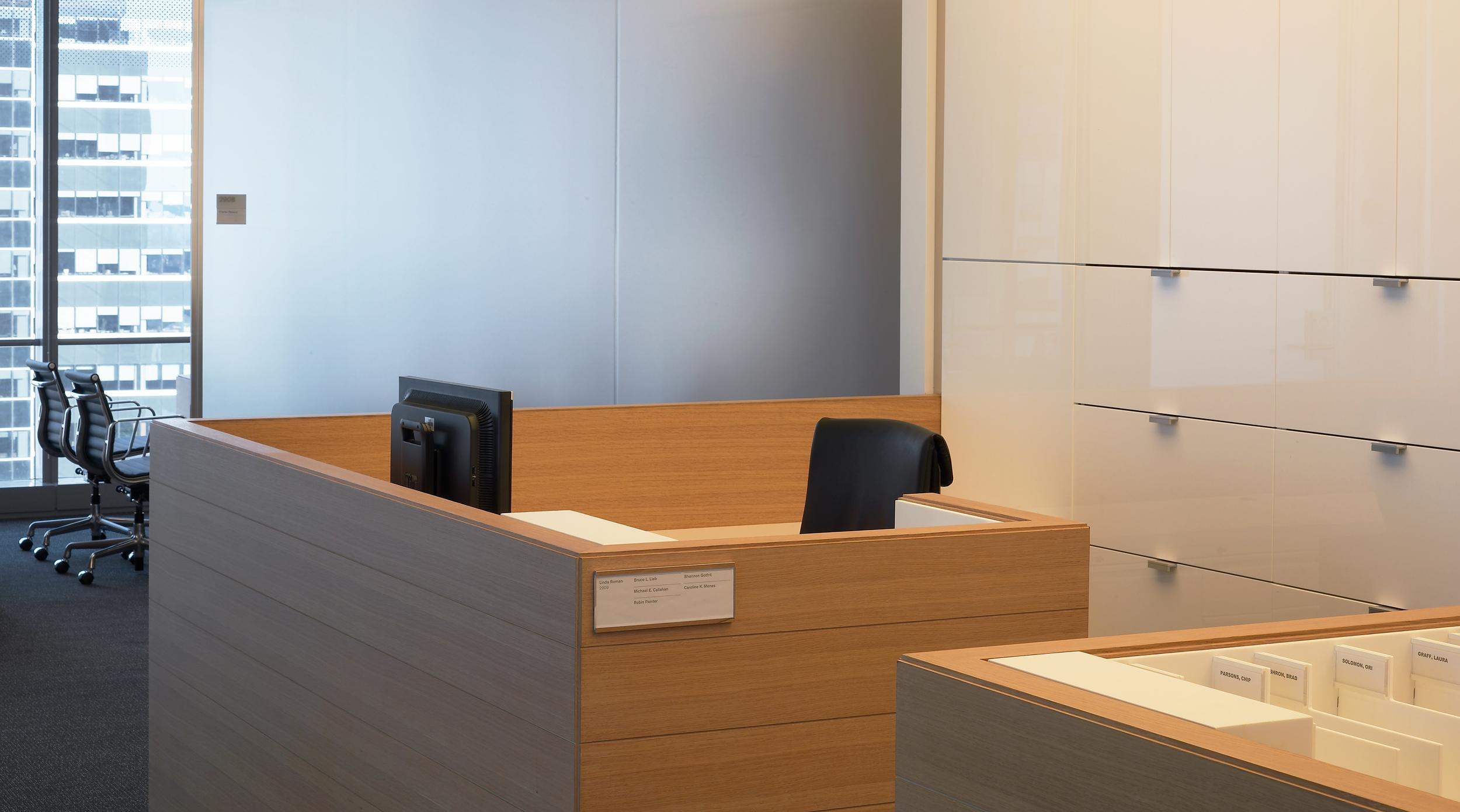 Custom secretarial stations feature Cerused Oak surrounds and high gloss white Parapan file fronts.