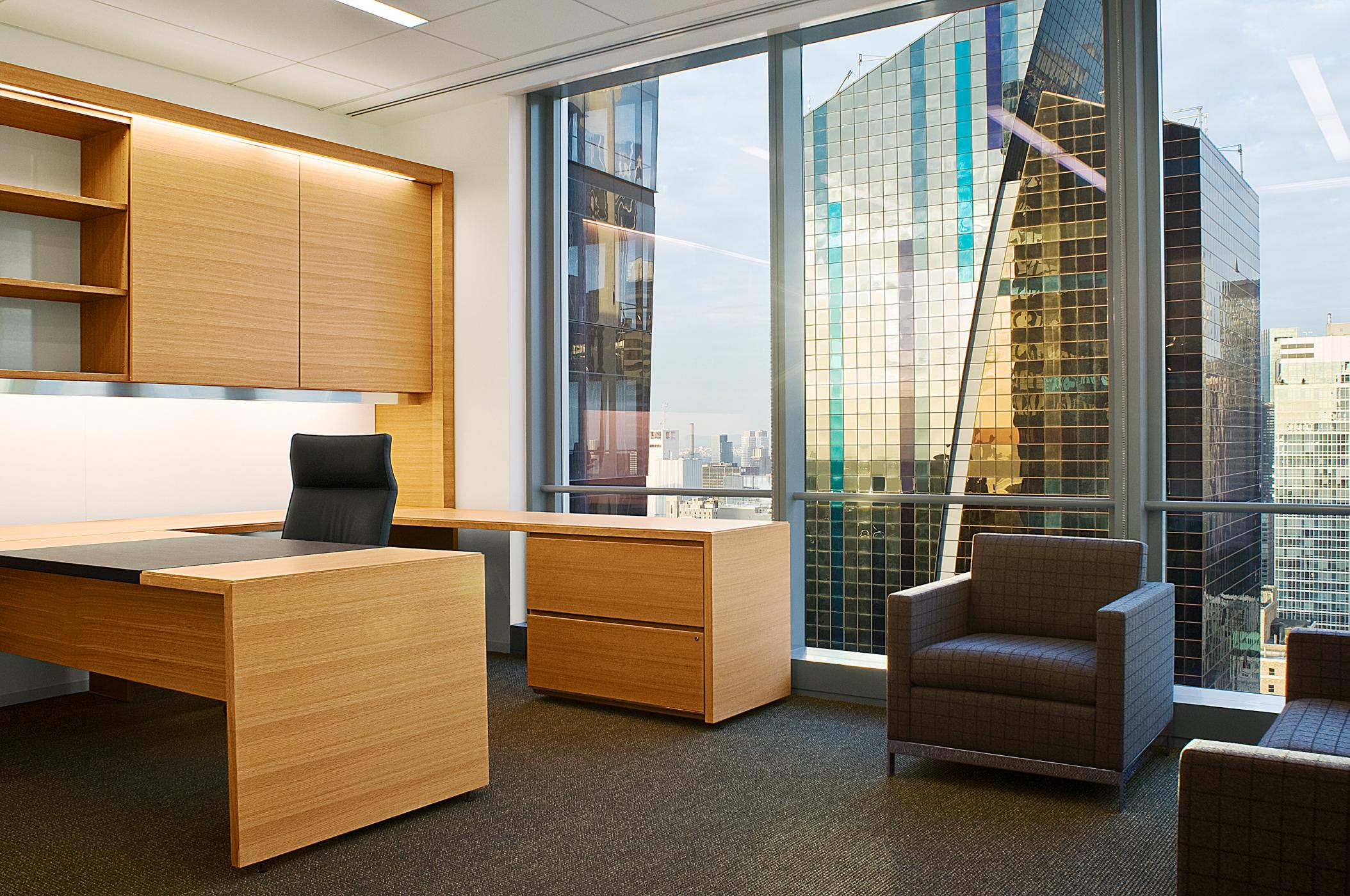 Offices incorporate cerused oak veneers, sliding doors, metal detailing, and integrated lighting.