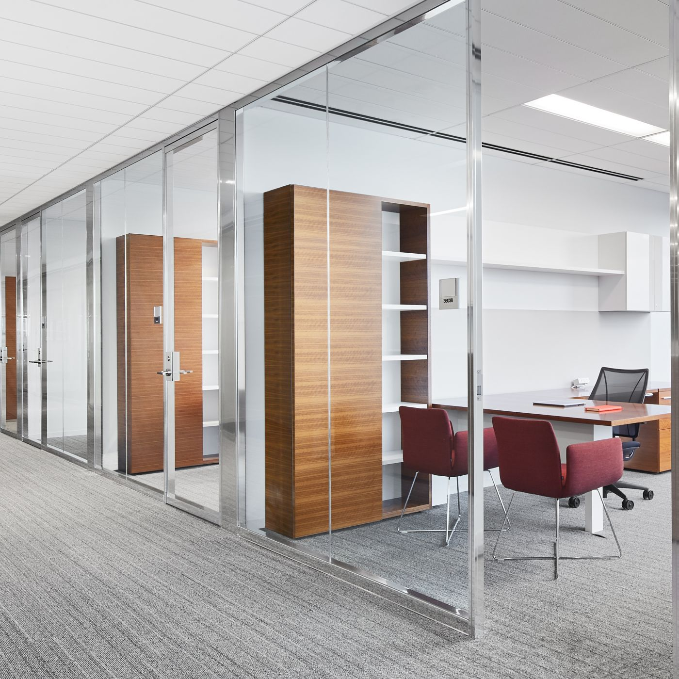 NEW MILLENNIA private offices feature a mix of open and closed storage in grain-matched Quarter Cut Walnut and White.