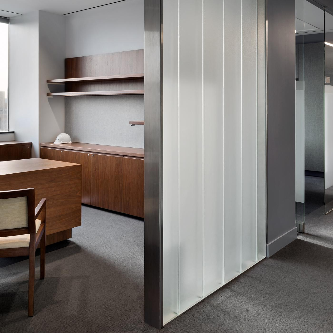 New Millennia private offices include adjustable-height desking and continuous floating shelves.